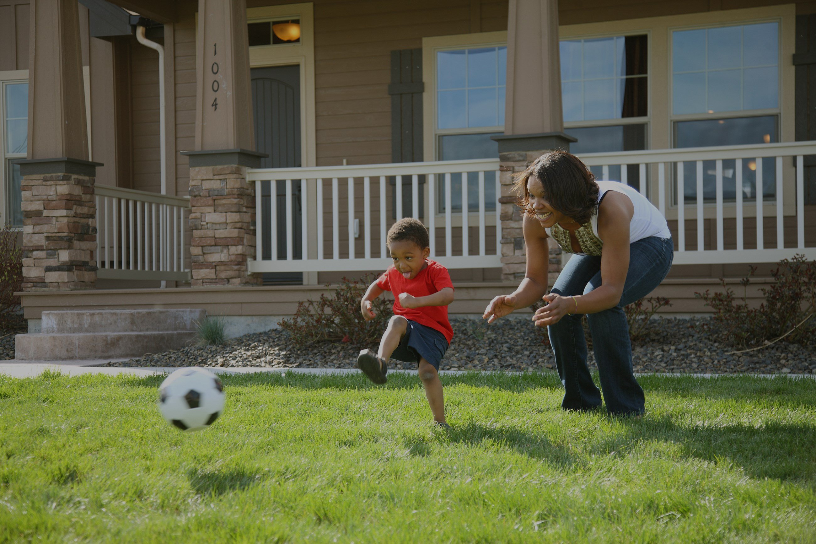 Family playing soccer outside of a new home.