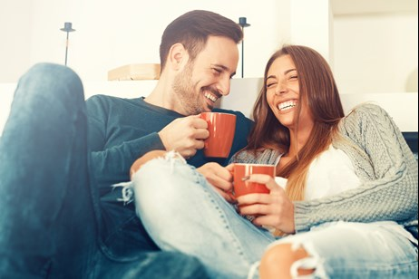 Couple laughs on couch together