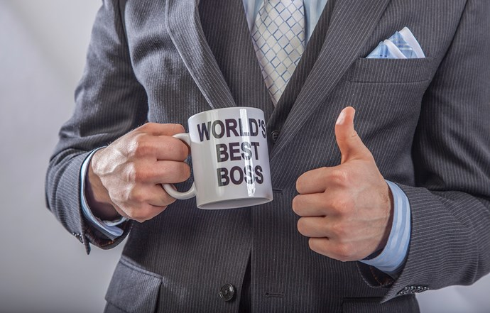 "Holding ""World's Best Boss"" mug"