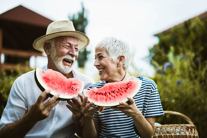 An older couple eating watermelon